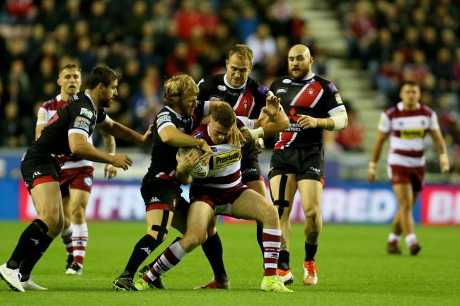 n Salford Reds' Lee Mossop helps to stop Wigan's Joe Burgess during the Betfred Super League semi final match	 Picture: PA
