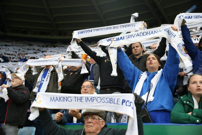 Leicester City fans lift their scarves in memory of former chairman Vichai Srivaddhanaprabha