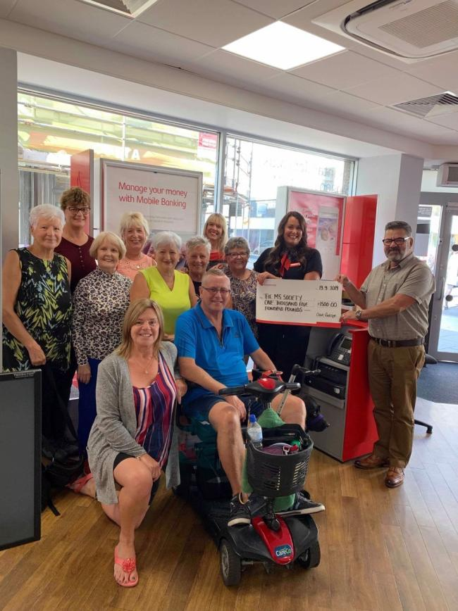 n Knitters and Santander staff present the cheque to the West Cumbria MS society
